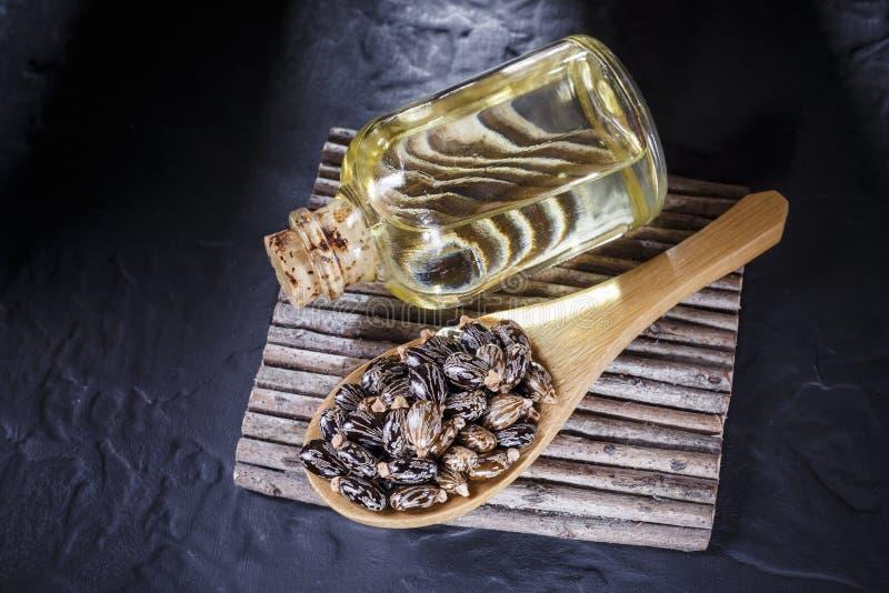 Bohnen und Rizinusöl auf der schwarzen Tabelle stockbilder
