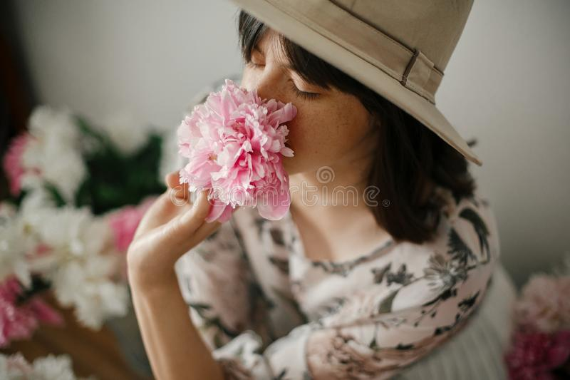 boho女孩嗅到的牡丹画象在桃红色和白色牡丹的在土气木地板上 漂泊礼服的时髦的行家妇女 免版税库存照片