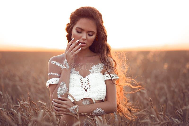 Boho chic stil Stående av den bohemiska flickan med vit konst som poserar över vetefält som tycker om på solnedgången Utomhus fot royaltyfri bild