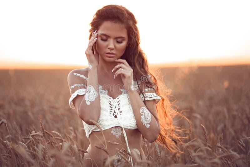 Boho chic stil Stående av den bohemiska flickan med vit konst som poserar över vetefält som tycker om på solnedgången Utomhus fot arkivfoton