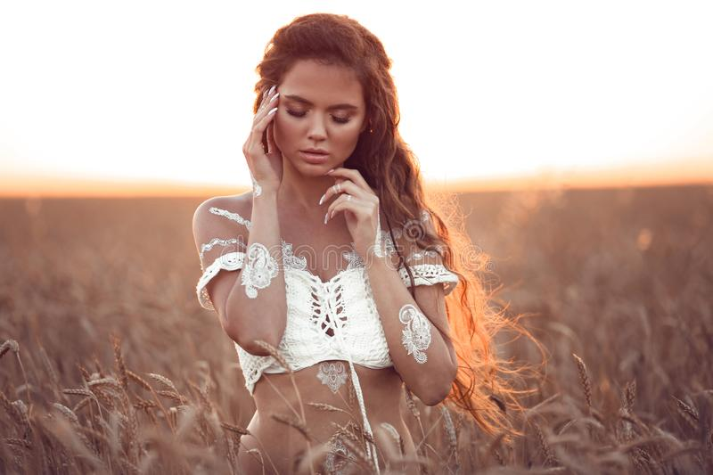 Boho chic style. Portrait of bohemian girl with white art posing over wheat field enjoying at sunset. Outdoors photo. Tranquility stock photos