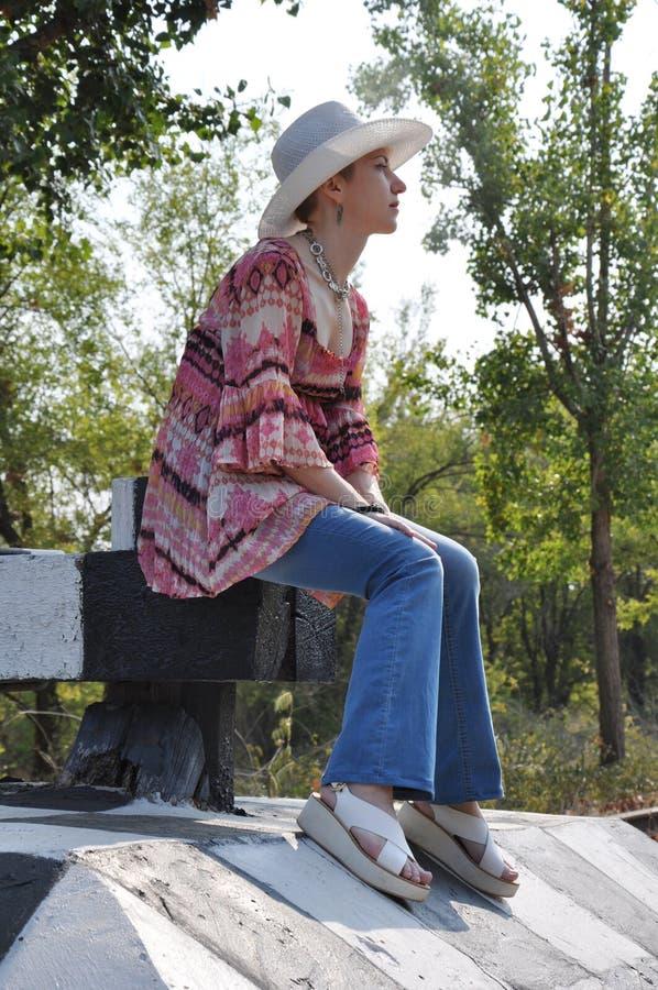 Boho de femme dans la verticale se reposante de chapeau photo stock