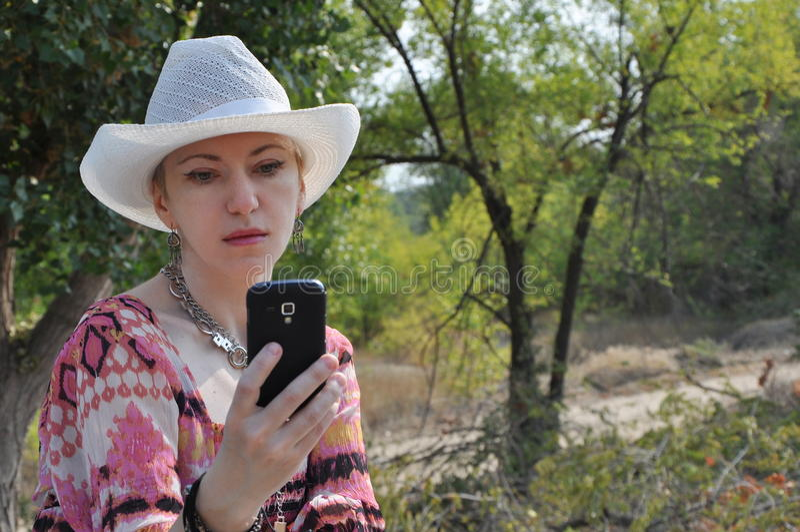 Boho de femme dans le chapeau avec le mobile photos stock