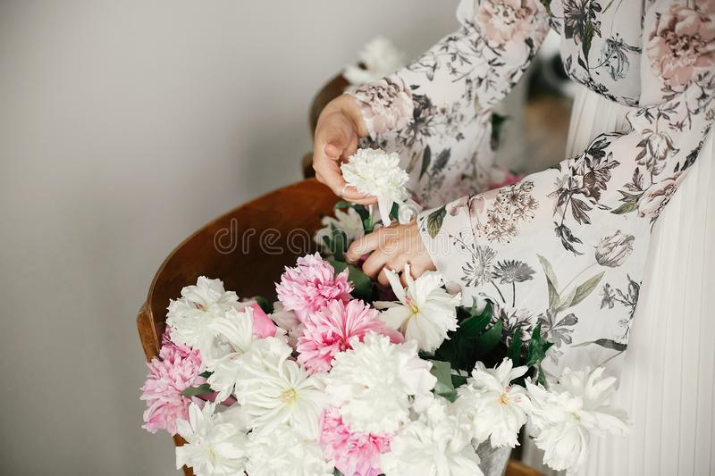 Boho girl holding pink and white peonies in hands at rustic wooden chair. Stylish hipster woman in bohemian dress arranging peony stock image