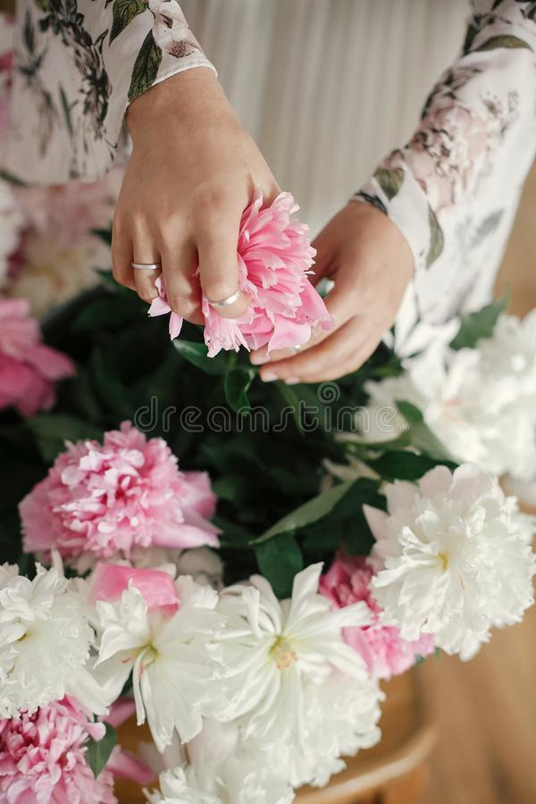 Boho girl holding pink and white peonies in hands at rustic wooden chair. Stylish hipster woman in bohemian dress arranging peony royalty free stock photos