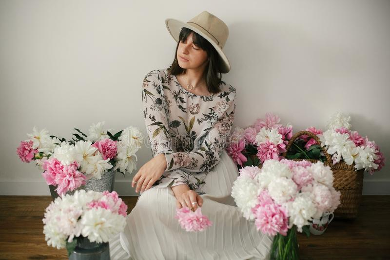 Boho girl sitting at pink and white peonies in rustic basket and metal bucket on wooden floor. Stylish hipster woman in bohemian royalty free stock photos