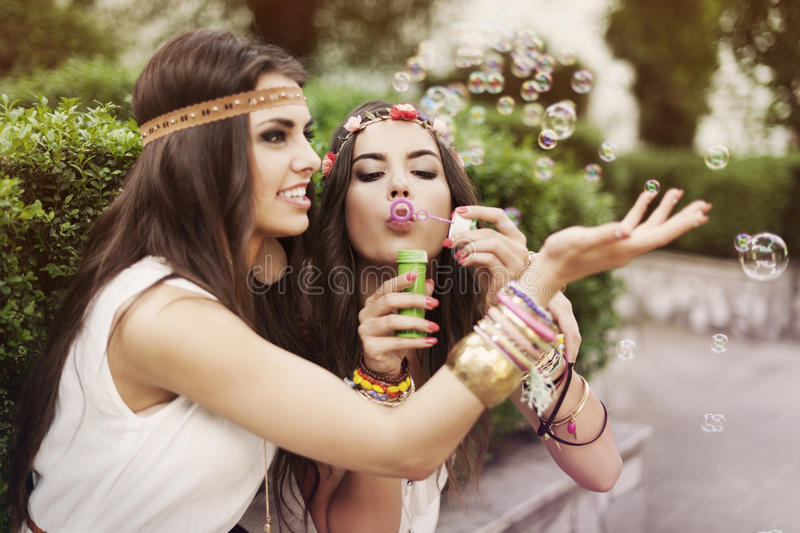 Boho girls playing with bubbles stock photo