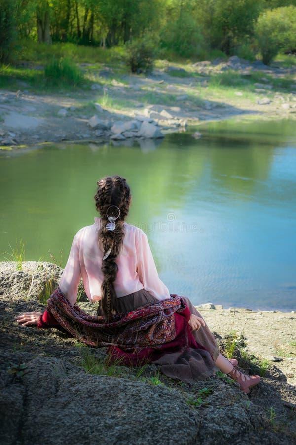 Boho hermoso de la mujer, sentándose en una roca en la orilla del río fotos de archivo libres de regalías