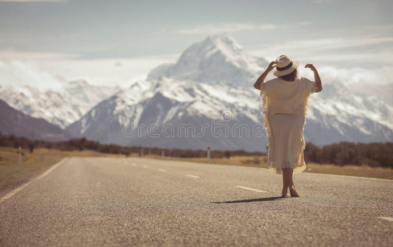 Boho hipisa dama w biel sukni z kapeluszy stojakami na drodze z ao zdjęcie stock