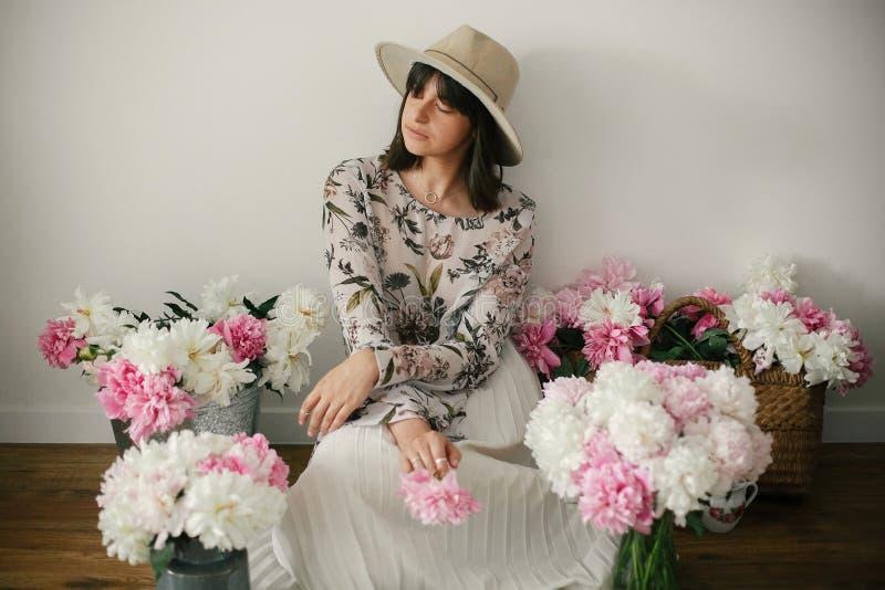 Boho-Mädchen, das an den Rosa- und weißenpfingstrosen im rustikalen Korb und im Blecheimer auf Bretterboden sitzt Stilvolle Hippi lizenzfreie stockfotos