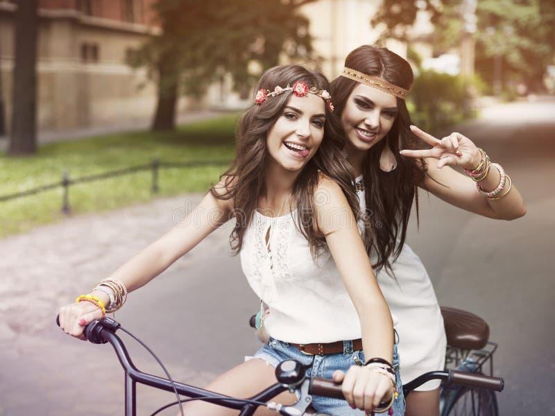 Boho-Mädchen, die auf Fahrrad fahren stockfoto