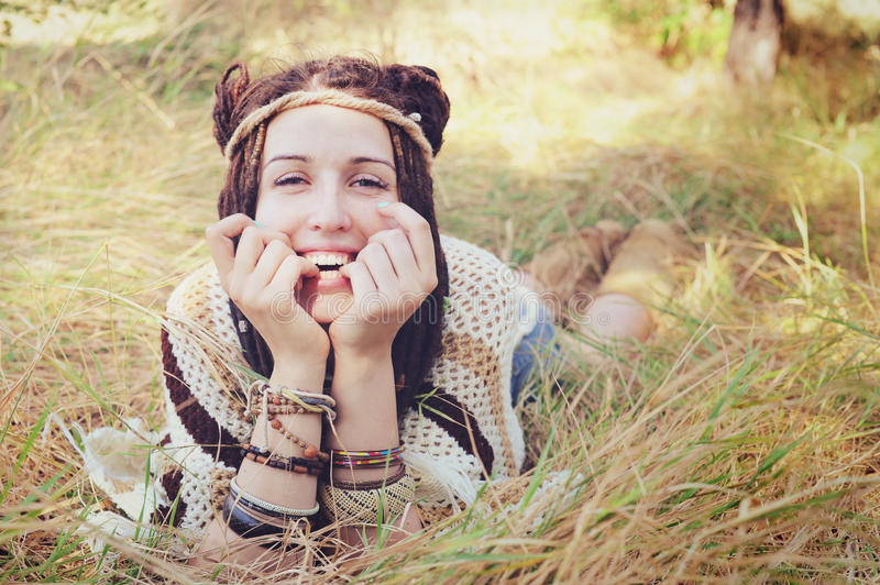 Boho style smiling woman portrait, girl have a fun lying outdoor in autumn sunny park. Natural lifestyle concept stock photo