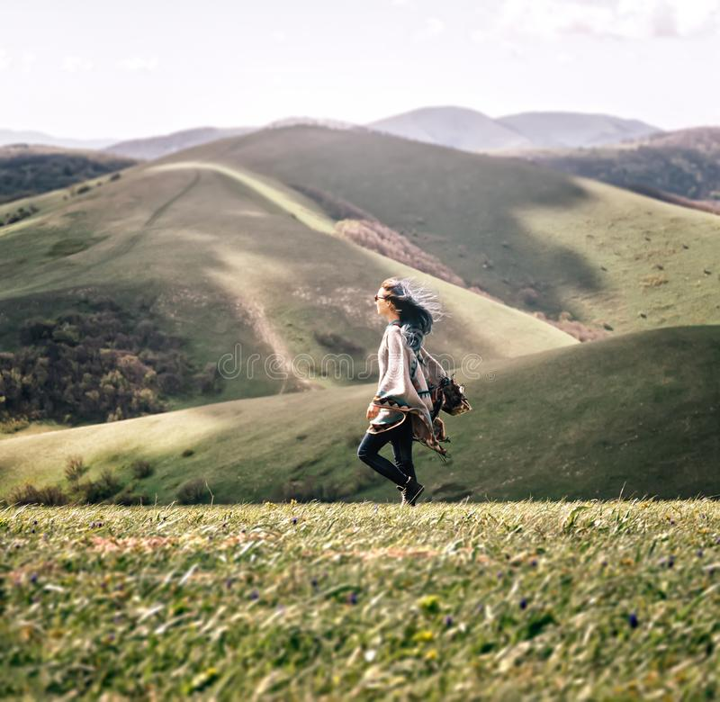 Woman walking in the mountains in windy weather. Boho style young woman walking in the mountains in windy weather stock photos