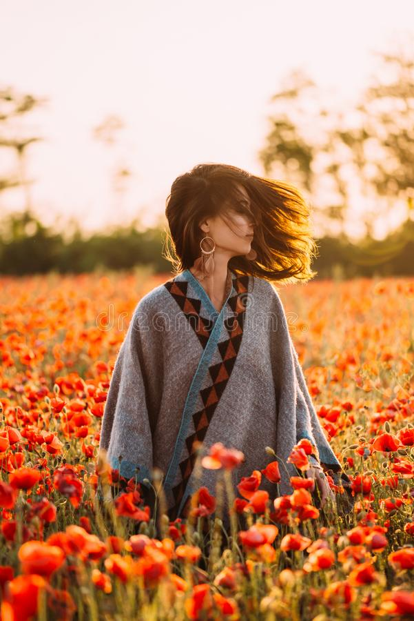 Boho stylish woman walking in red poppies meadow. royalty free stock images