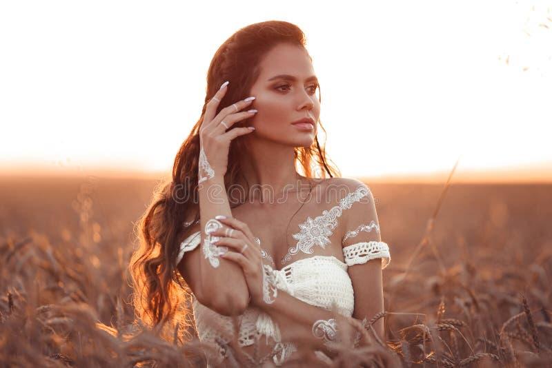 Boho szyka styl Portret artystyczna dziewczyna z białą sztuką pozuje nad pszenicznym polem cieszy się przy zmierzchem Outdoors fo fotografia stock