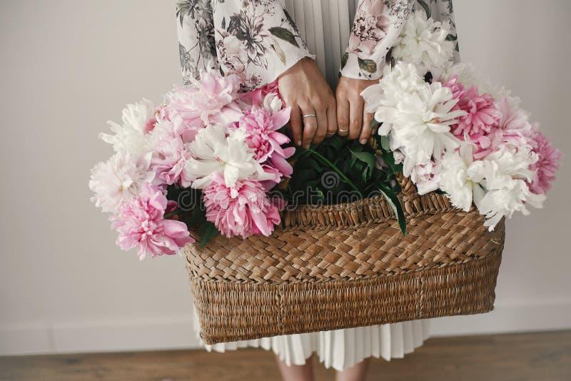 Bohomeisje die roze en witte pioenen in rustieke mand houden Modieuze hipstervrouw die in Boheemse bloemenkleding pioenbloemen ve royalty-vrije stock foto's