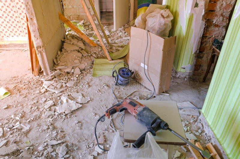 Bohren Sie auf den schmutzigen und staubigen Boden in ein Haus im Bau stockbild