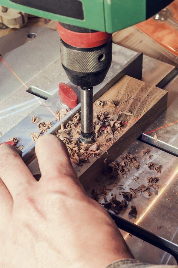 Bohren Sie eine Mühle für einen Baum in die Bohrmaschine mit einer Laser-Markierung Handmeister bohrt ein Loch in einer hölzernen lizenzfreie stockfotografie