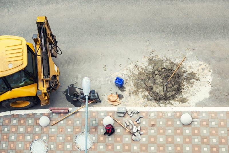 Bohrende Straße des großen Jackhammerbohrgeräts Schwermaschinen, die Asphalt für Regenwasserabflussreparatur zerquetschen lizenzfreie stockbilder