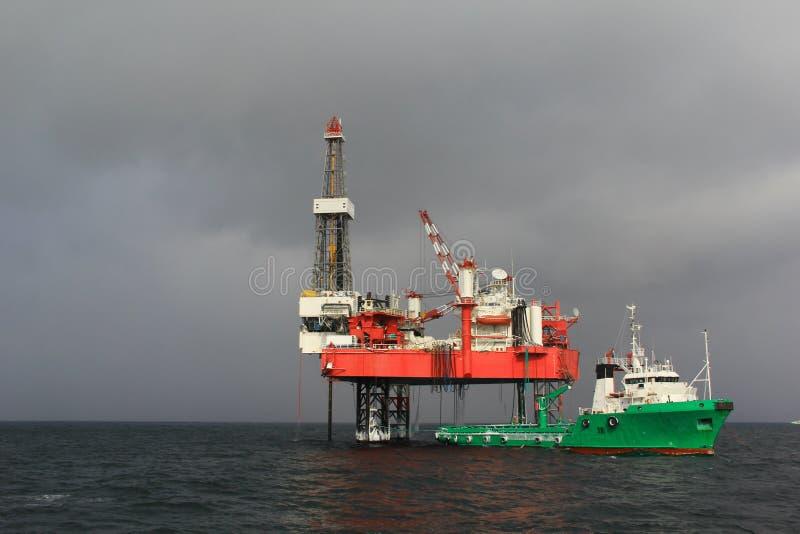 Bohrinsel mit Versorgungsschiff lizenzfreie stockbilder