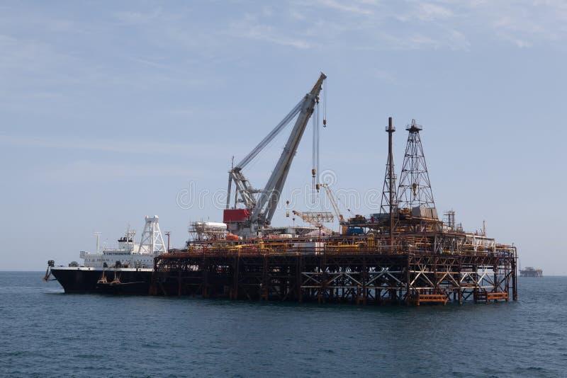 Bohrinsel und Tanker stockbild