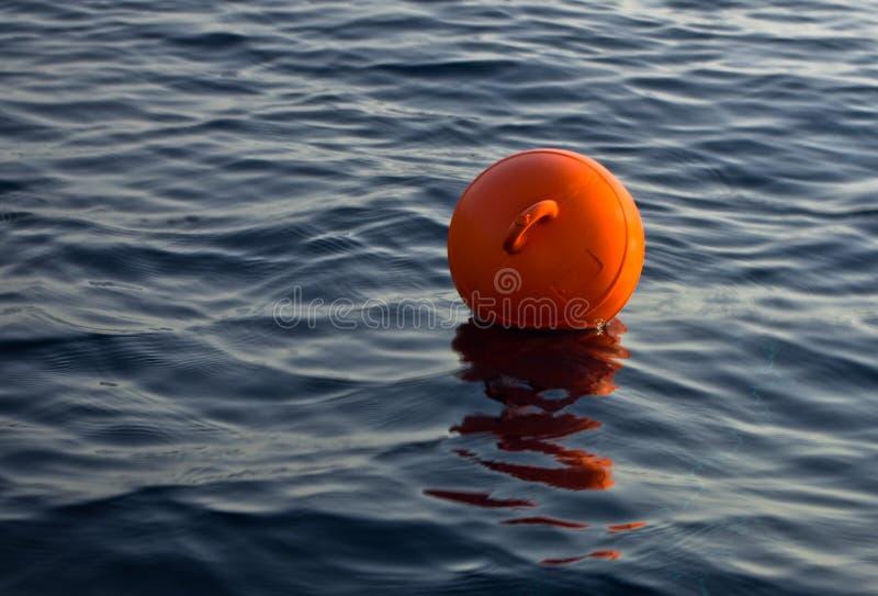 Boia alaranjada que flutua em uma obscuridade - mar azul da pesca no por do sol imagens de stock