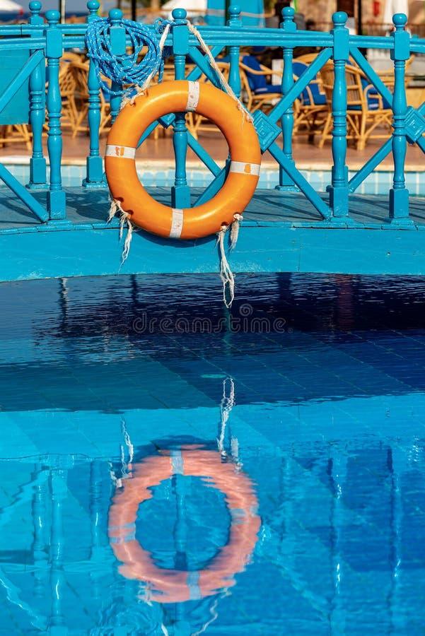 Boia salva-vidas alaranjado com cordas em uma piscina fotografia de stock