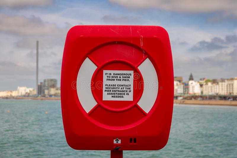 Boia salva-vidas e sinal de aviso com skyline de Brigghton no backgroun fotos de stock royalty free