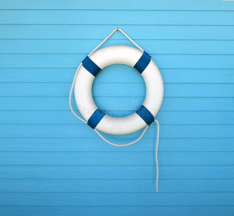 Boia salva-vidas em uma parede azul imagens de stock