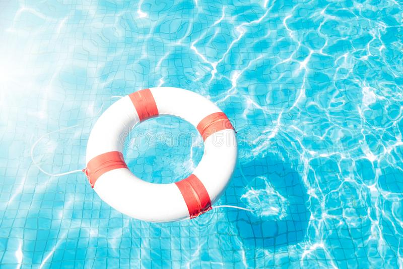 Boia salva-vidas que flutua na piscina azul fotografia de stock