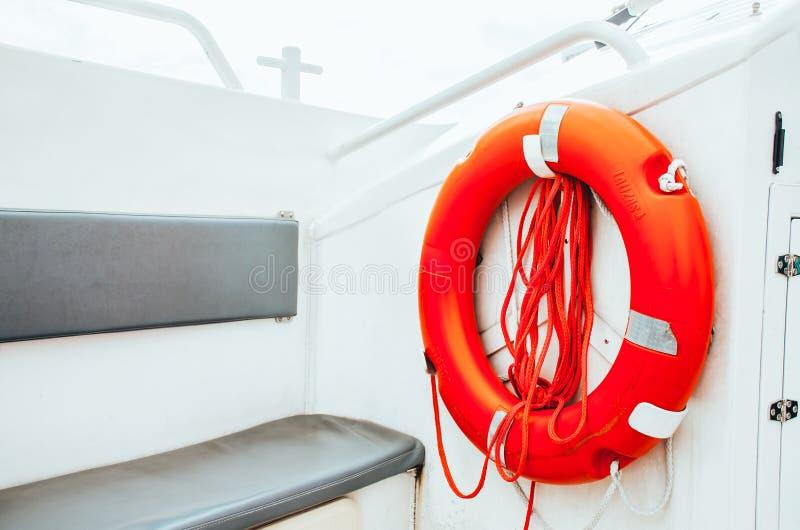 Boia salva-vidas vermelho com a corda que pendura em uma parede exterior do tapume pintado branco no barco imagens de stock royalty free