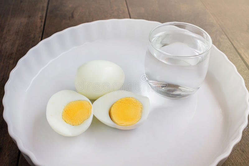 Boil eggs on white plate with glass of water in morning meal fee. Ling, diet food stock photo