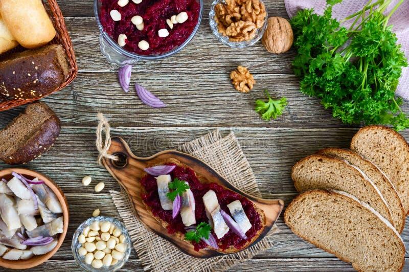 Boiled磨碎了甜菜,鲱鱼,红洋葱,在整个五谷面包的坚果片断  免版税库存图片