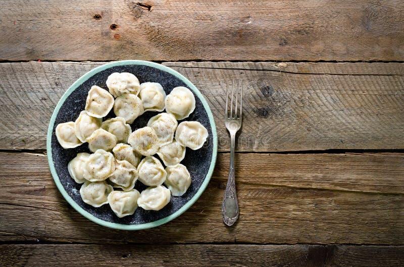 Boiled подготовило домодельное русское pelmeni, вареники, равиоли с мясом на серой плите с свежей петрушкой, перцем, деревянным стоковое фото