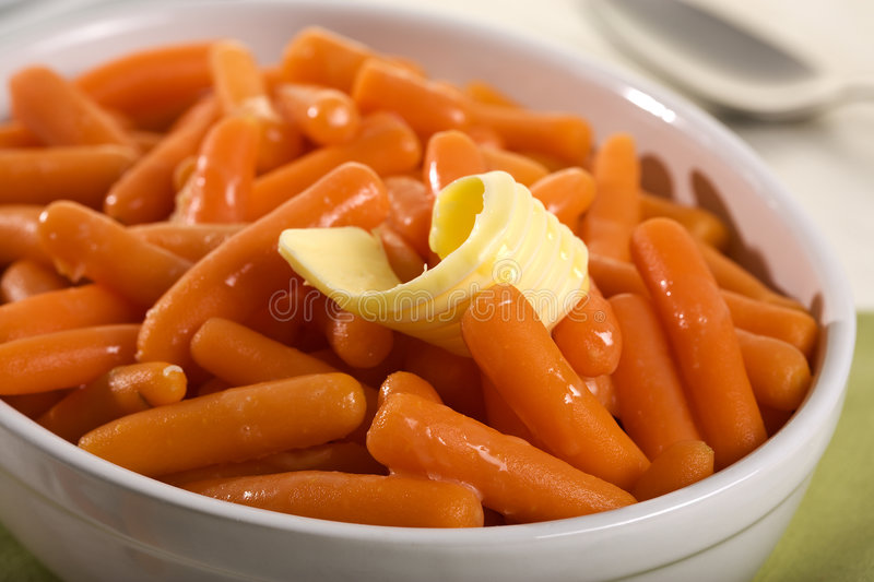 Boiled baby carrots and curl of butter royalty free stock photos