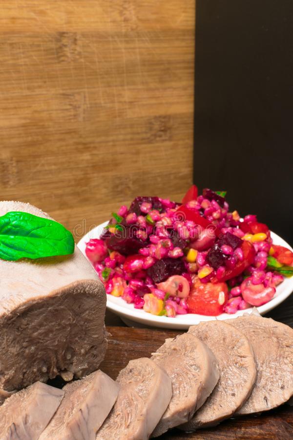 Boiled beef or pork tongue with beet- mushrooms -champignon salad, basil leaf, studio shot, isolated on wood background. Top view. Boiled beef or pork tongue royalty free stock images