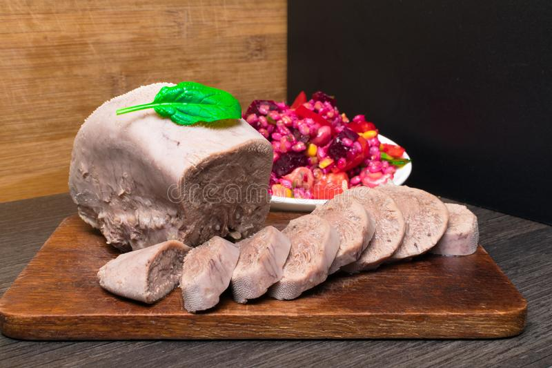 Boiled beef or pork tongue with beet- mushrooms -champignon salad, basil leaf, studio shot, on wood background. Top view. Boiled beef or pork tongue with cherry royalty free stock images