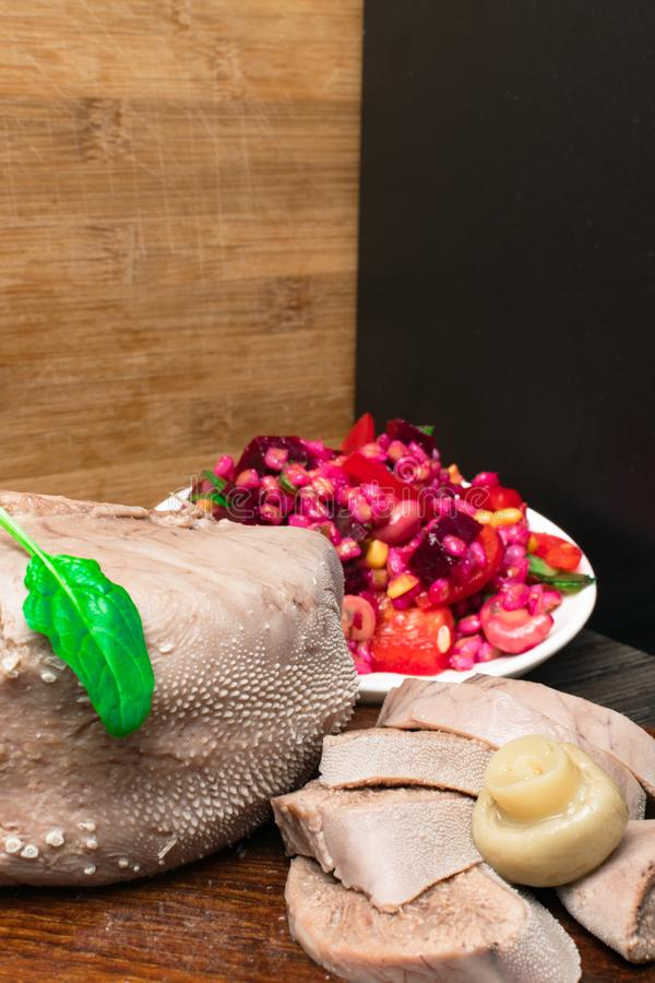 Boiled beef or pork tongue with beet- mushrooms -champignon salad, basil leaf, studio shot, on wood background. Top view. Boiled beef or pork tongue with cherry royalty free stock photos