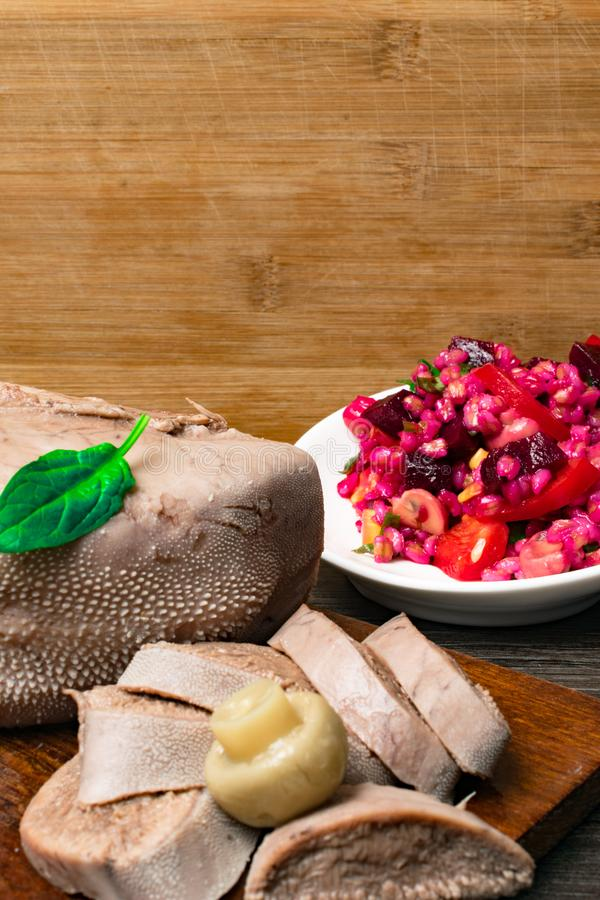 Boiled beef or pork tongue with beet- mushrooms -champignon salad, basil leaf, studio shot, on wood background. Top view. Boiled beef or pork tongue with cherry stock photos