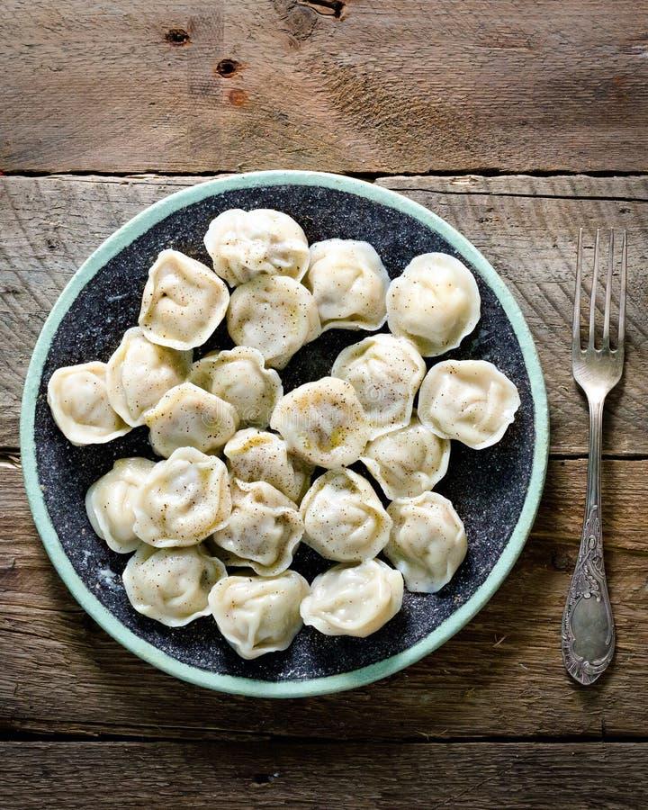 Boiled bereitete selbst gemachtes russisches pelmeni, Mehlklöße, Ravioli mit Fleisch auf grauer Platte mit frischer Petersilie, d lizenzfreies stockbild