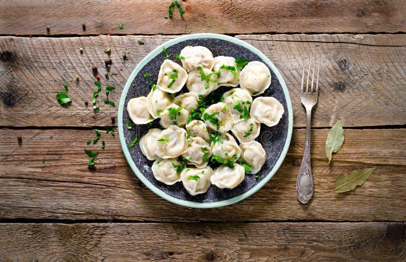 Boiled bereitete selbst gemachtes russisches pelmeni, Mehlklöße, Ravioli mit Fleisch auf grauer Platte mit frischer Petersilie, d lizenzfreies stockfoto