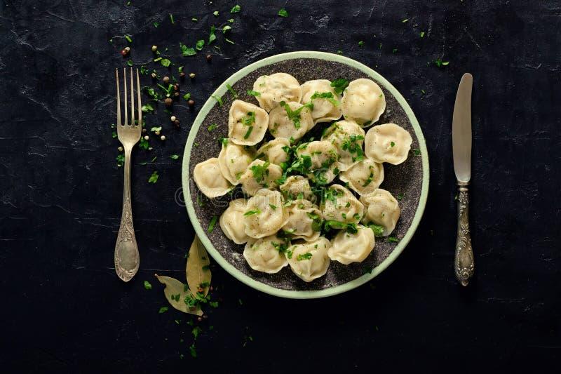 Boiled bereitete selbst gemachtes russisches pelmeni, Mehlklöße, Ravioli mit Fleisch auf grauer Platte mit frischer Petersilie, P stockfoto