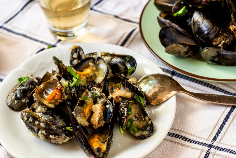 Boiled black mussels on two plates, garlic and vine on table royalty free stock photo