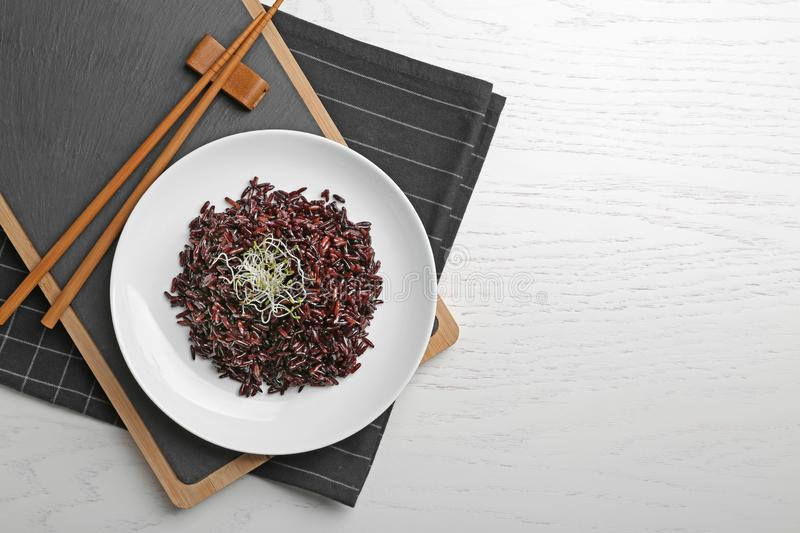 Boiled brown rice with sprouted flax seeds served on table, top view. Space for text stock image