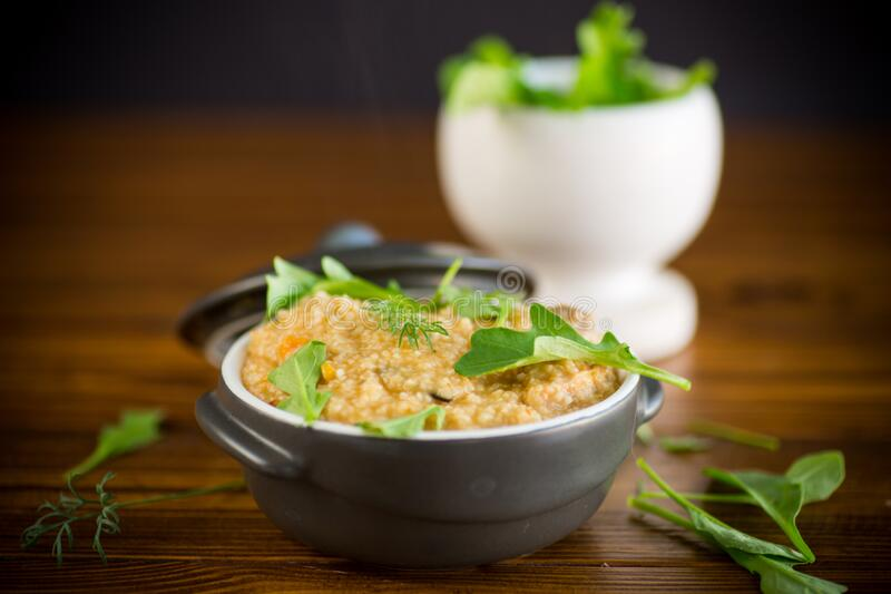 Boiled bulgur groats with vegetables and herbs. In a ceramic bowl royalty free stock photo