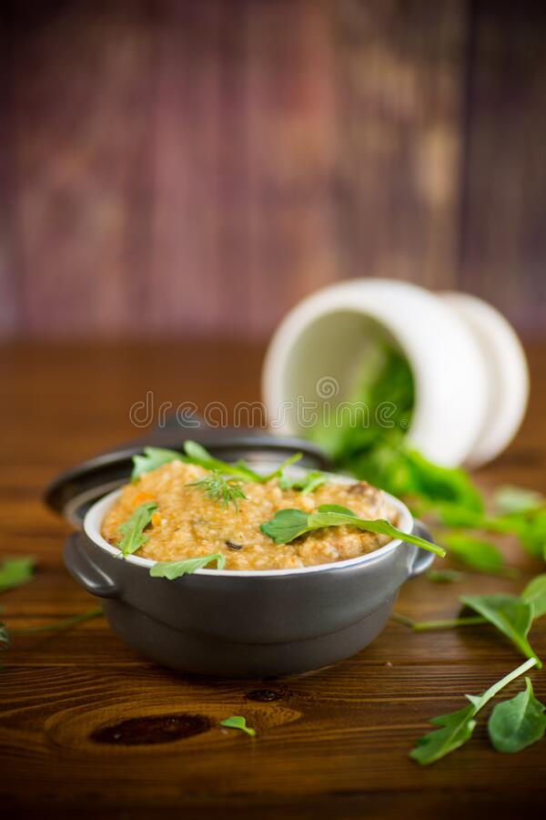 Boiled bulgur groats with vegetables and herbs. In a ceramic bowl royalty free stock image
