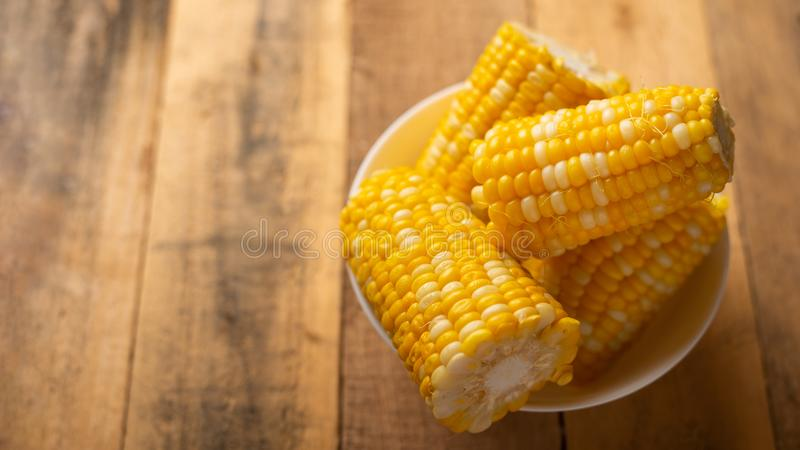 Boiled corn cob in a plate with butter, on a wooden texture, delicious homemade food, for a picnic stock photo