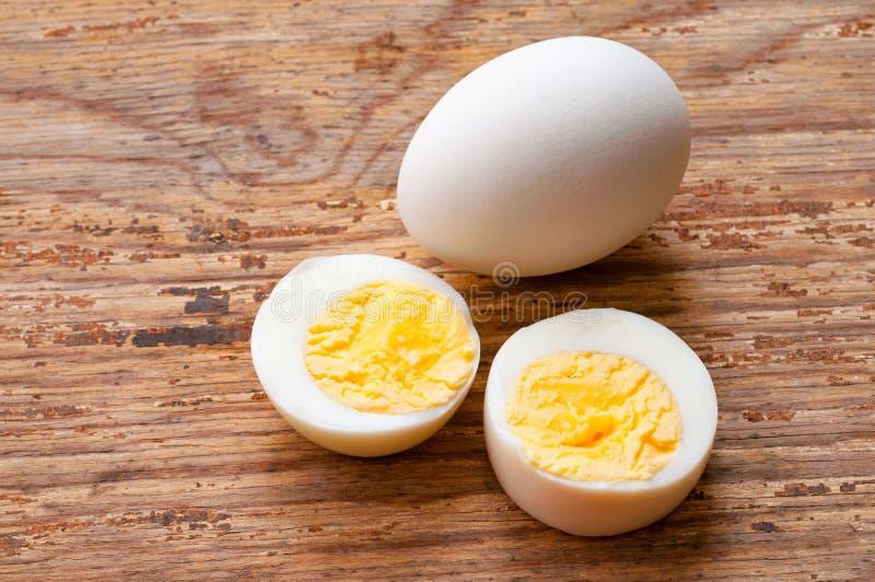 Boiled cortou ovos da galinha na tabela de madeira imagem de stock