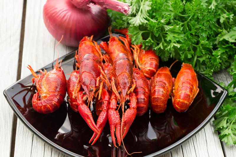Boiled crawfish. Woden background. Rustic style. Red boiled crawfish on the black rectangular plate. Red boiled crawfish on the black rectangular plate. Boiled royalty free stock photo