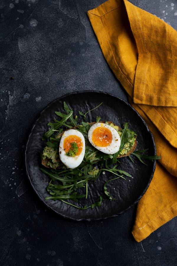 Boiled egg on arugula salad with grain bread on black plate with orange napkin stock image